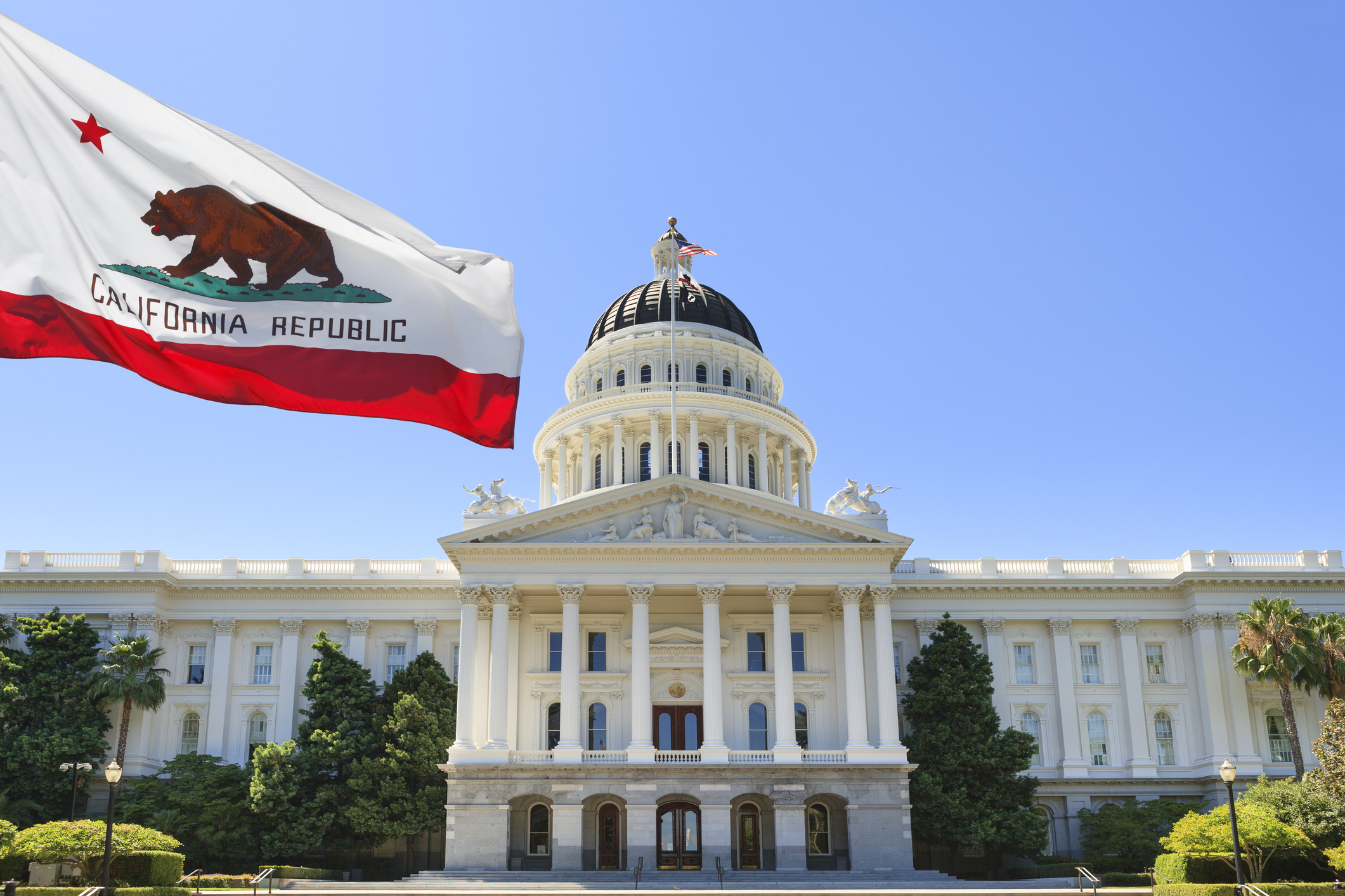 California state flag flying in front of capital building in Sacramento