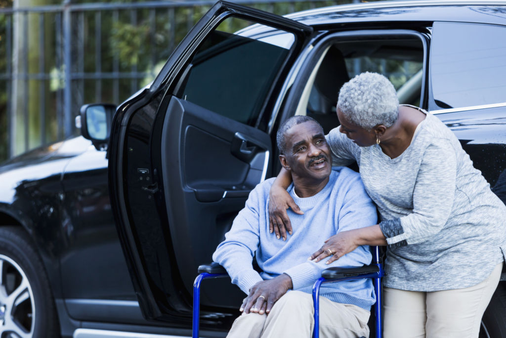 A disabled senior African American man has gotten out of a car, and is sitting in his wheelchair. His loving wife is talking to him with her arm around his neck.