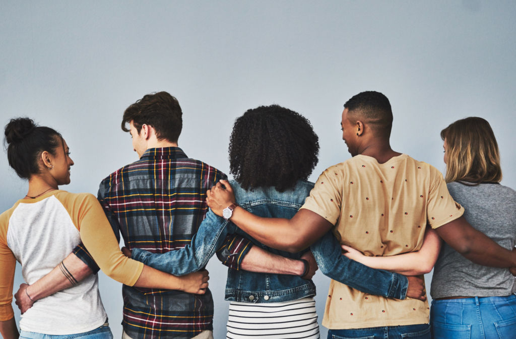 Rearview studio shot of a diverse group of young people embracing each other against a gray background