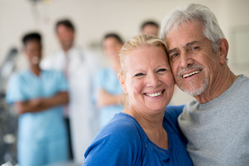 Portrait of senior couple at the clinic leaninig their heads together and looking at the camera smiling while a team of doctors and nurses are standing at the background