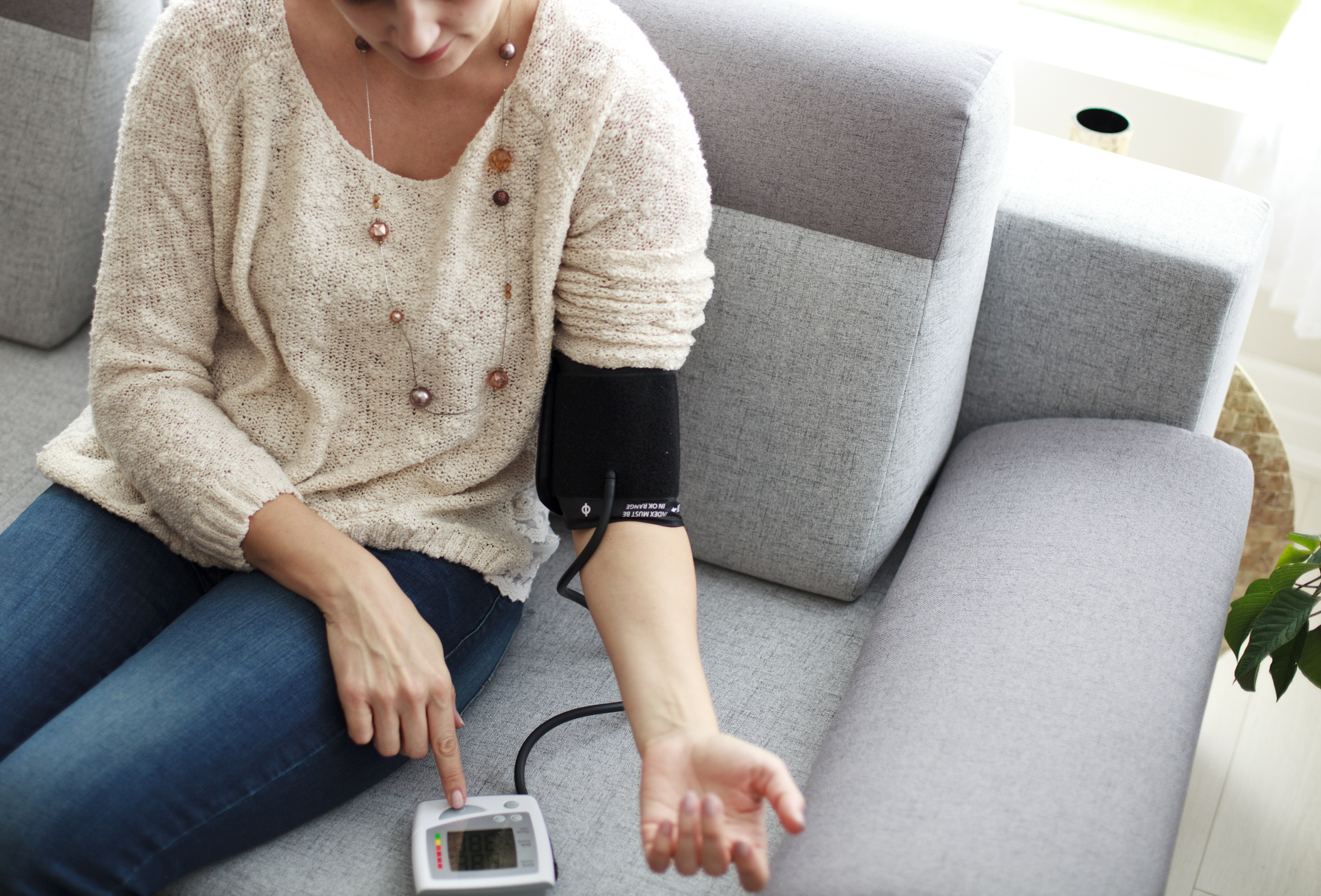 Woman measuring her blood pressure at home