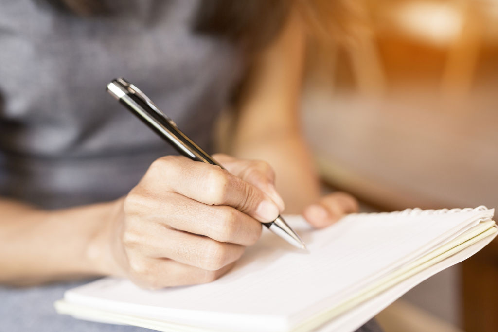Women holding a pen while writing in a notebook.